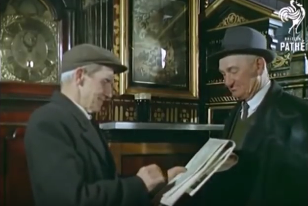 Two gentlemen reading the paper in 1965. A painting on display in the background