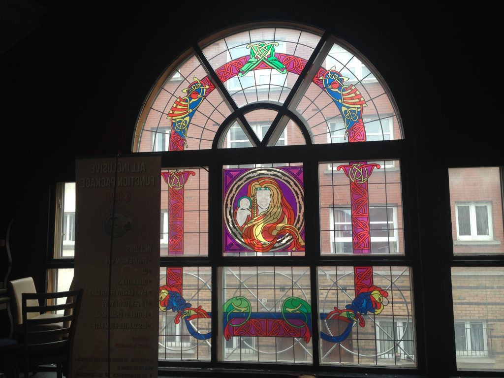 The stained glass window is behind the stage area.